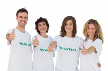 Cheerful group of volunteers giving thums up on white background