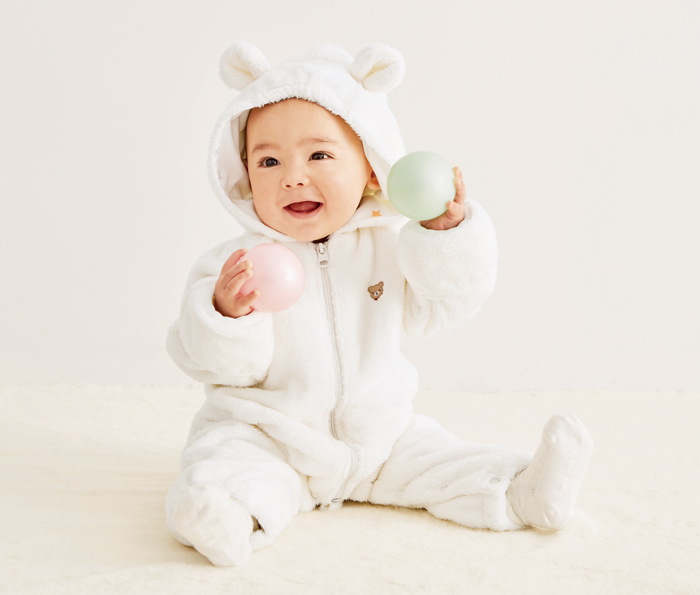 マイクロファーカバーオールを着た、かわいい赤ちゃん