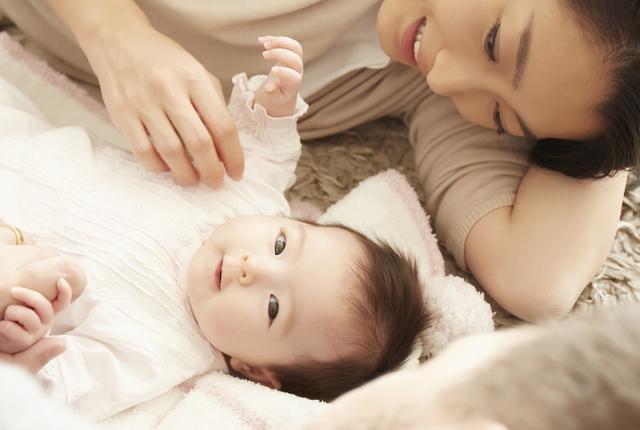 寝そべる赤ちゃんのママ