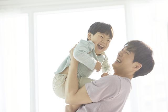 子どもを抱き上げるパパ