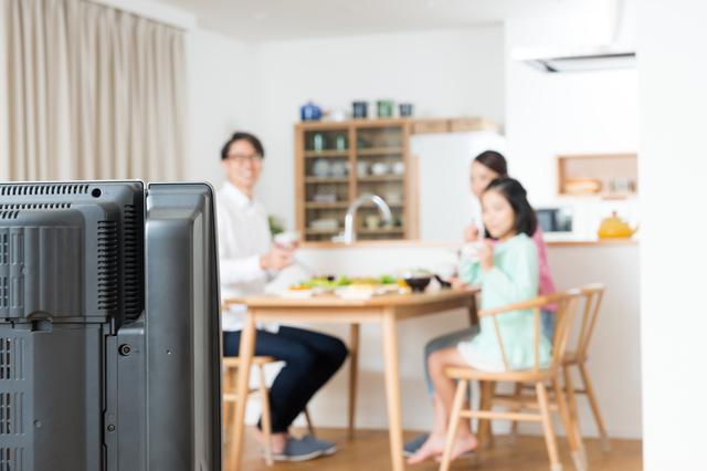 テレビを見ながら食事をする家族