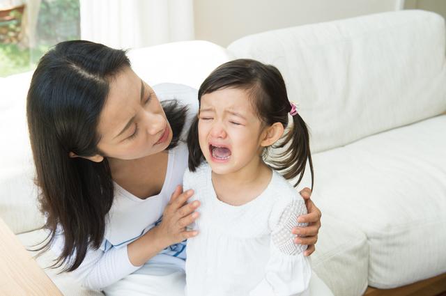 泣く子どもの話を聞くお母さん