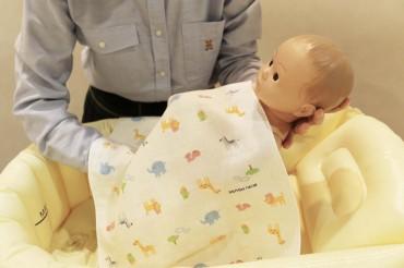③ガーゼを赤ちゃんの上にかけて足先からお湯に